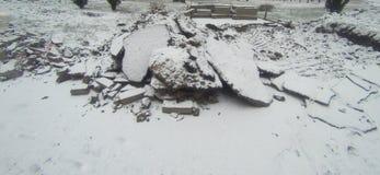 Stukken van gebroken die asfalt met sneeuw wordt behandeld Royalty-vrije Stock Foto's