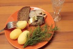 Stukken van gerookt hardhead met een aardappel en een wijnglas wodka Stock Afbeelding