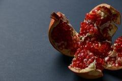 Stukken van granaatappel op een zwarte achtergrond Vitaminen en Mineralen royalty-vrije stock afbeeldingen