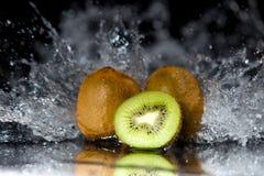Stukken van kiwi met waterplonsen en bezinning over zwarte bac Royalty-vrije Stock Foto's