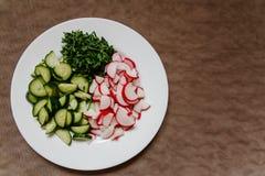 Stukken van komkommer en verse radijs op een witte plaat stock foto's