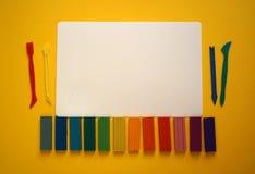 Stukken van multicolored plasticine voor kinderen tegen een gele achtergrond stock foto's