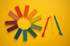 Stukken van multicolored plasticine voor kinderen tegen een gele achtergrond stock foto
