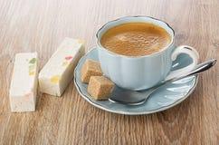 Stukken van noga met marmelade, koffie in kop, suiker, lepel op schotel op lijst royalty-vrije stock afbeelding