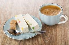 Stukken van noga met marmelade, suiker, lepel op schotel, koffie in kop op lijst royalty-vrije stock foto's