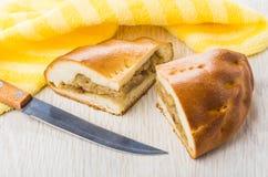 Stukken van pastei met kool, geel servet en keukenmes Stock Fotografie