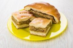 Stukken van pastei met kool in gele plaat op lijst Stock Fotografie