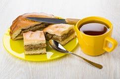 Stukken van pastei met kool in plaat, mes, theelepeltje, thee Royalty-vrije Stock Afbeeldingen