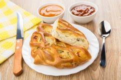 Stukken van pastei in plaat, keukenmes, sausen in kommen Royalty-vrije Stock Fotografie