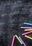 Stukken van schoolkrijt op oud zwart bord royalty-vrije stock afbeeldingen