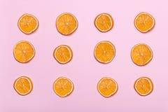 Stukken van sinaasappel Cirkels met sinaasappel Roze achtergrond Citroenen, sinaasappelen en kalk Stock Foto