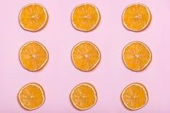 Stukken van sinaasappel Cirkels met sinaasappel Roze achtergrond Citroenen, sinaasappelen en kalk Royalty-vrije Stock Fotografie