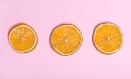 Stukken van sinaasappel Cirkels met sinaasappel Roze achtergrond Citroenen, sinaasappelen en kalk Stock Fotografie