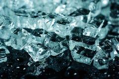 Stukken van verpletterd ijs op zwarte achtergrond met waterdalingen Stock Afbeeldingen
