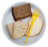 Stukken van wheaten en roggebrood op een witte plastic plaat Stock Fotografie