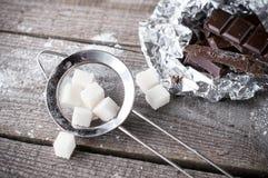 Stuksuiker in een metaalzeef en zwarte donkere chocoladestukken o Stock Fotografie