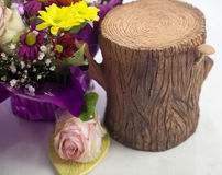 Stump of clay next to a bouquet flowers Stock Photo