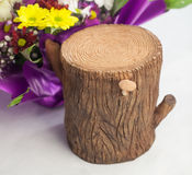 Stump of clay next to a bouquet flowers Stock Photos