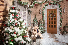 Stumps path leeding to the door of winter house with Christmas wreath. Hanging on it. Decorated trees, snow, garlands and New Year lights at background stock images