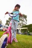 Stund för flickaridningsparkcykel på campa ferie för familj arkivbilder