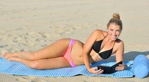 Stuning junge Frau auf Strand - Lesung im Bikini Lizenzfreie Stockfotos