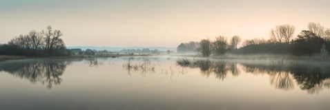 Stuning tranquil landscape panorama of lake in mist Royalty Free Stock Photography