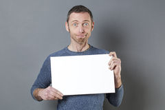 Stunned смотря человек 40s наслаждаясь делающ рекламу в показе пустой вставки Стоковое Фото