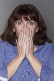 Stunned attractive mature woman hiding her mouth Stock Photo