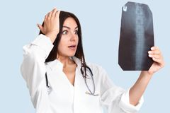 Stunned beautiful brunette young professional female doctor holds hand on head, holds X ray picture, studies backbone, shocked to stock image
