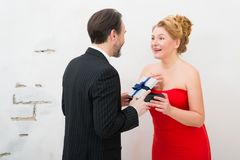 Stunned beautiful woman opening unexpected present from her husband royalty free stock photos