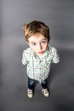 Stunned beautiful young boy staring for surprise, high angle view. Stunned beautiful young 6-year old boy staring with wide-eyed standing for speechless surprise Stock Images