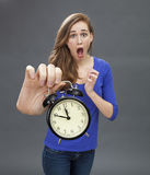 Stunned beautiful young woman for emphasis on deadline problem. Stunned beautiful young woman standing with an alarm clock in her oversized hand for emphasis on Royalty Free Stock Images