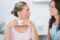 Stunned blonde looking at her quiet friend Stock Image