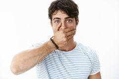 Stunned and concerned handsome guy feeling intense and worried covering mouth with palm as realising saying stupid. Things feeling shocked, recalling what stock image