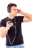 Stunned curious man listening something on mobile over headphone Royalty Free Stock Photography