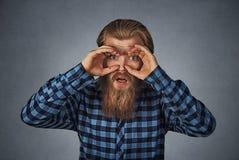 Stunned curious man looking through fingers like binoculars royalty free stock photo