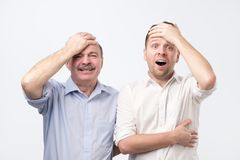 Stunned emotive two men keep jaw dropped, holding hand on head, wonder seasonal discounts and prices. Stand next to each other, isolated on white background stock photo