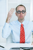 Stunned man with big glasses and a red tie at work like a comedi Royalty Free Stock Photo