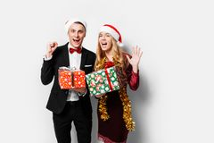 A stunned pair of lovers in Santa Claus hats celebrating the new stock photography