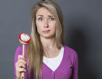 Stunned 20s girl with dish brush in hand unhappy at washing and cleaning Stock Images