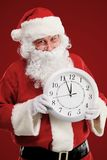 Stunned Santa holding clock showing five minutes to midnight Stock Image