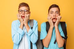 Stunned, shocked, two guys, teenagers are choking with fear, cover their mouths with both hands, on a yellow background. Stunned, shocked, two guys, teenagers stock image