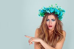 Stunned woman with floral headband pointing with index finger to copyspace royalty free stock image