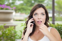 Stunned Young Adult Female Talking on Cell Phone Outdoors Royalty Free Stock Photo
