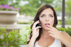 Stunned Young Adult Female Talking on Cell Phone Outdoors Royalty Free Stock Images