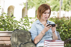 Stunned Young Female Student Outside Texting on Cell Phone. Stunned Young Pretty Female Student Outside with Backpack and Books Sitting on Bench Texting on Cell Stock Images