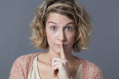 Stunned young woman playing confidential and taboo with face expression Royalty Free Stock Image