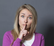 Stunned young woman wanting to keep things quiet and confidential Royalty Free Stock Photo