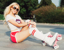 A stunner smiling summer closeup portrait of young happy woman posing in a vintage roller skates, sunglasses, T-shirt shorts Stock Images