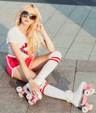A stunner smiling summer closeup portrait of sexy young happy woman posing in a vintage roller skates, sunglasses, T-shirt shorts Stock Image